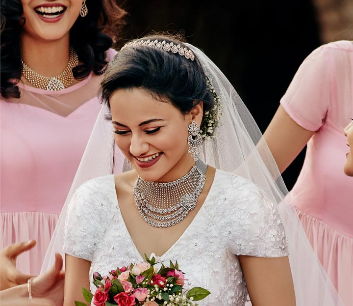 Gorgeous Smiling Bride With His Bridemaids In White Gown With Bouquet In Hands.