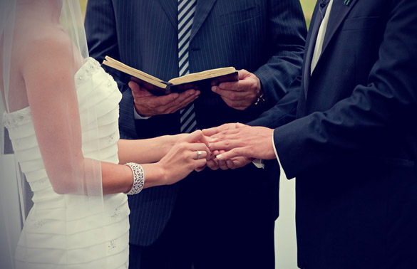 Bride and Groom Holding Hands With Each Other While Priest Reading The Wedding Vows.